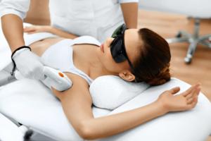 Laserbehandlung einer Frau, die sich die Achselhaare im Kosmetikstudio entfernen lässt.